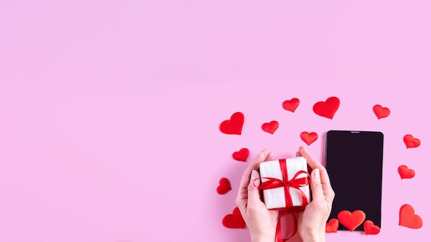 Hands hold a gift with a red ribbon over a black blank screen of a tablet or phone with red heart shape