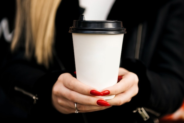 Hands  hold paper cup with coffee or tea. takeaway drink concept
