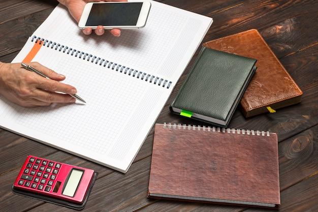 手はペンとスマートフォンを持ち、ノートブックを開きます。テーブル電卓とノートブック。上面図。