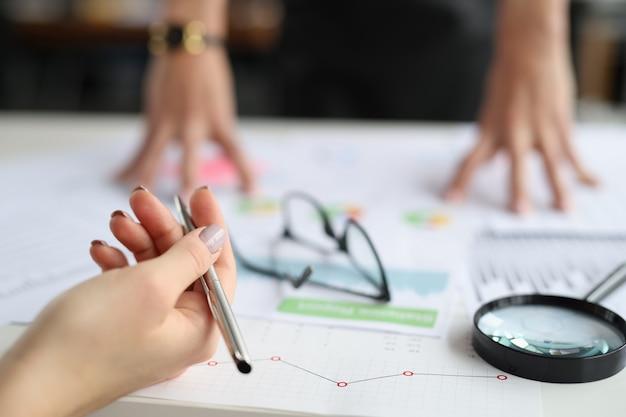 테이블에 펜을 들고 있는 손은 상업 차트와 돋보기 중소기업입니다