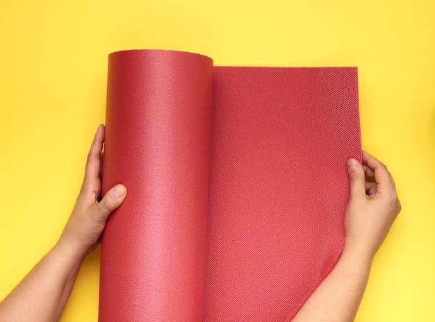 Руки держат красный коврик для йоги