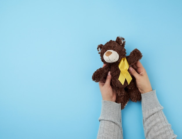 Hands hold a small brown teddy bear which holds in its paw a yellow ribbon