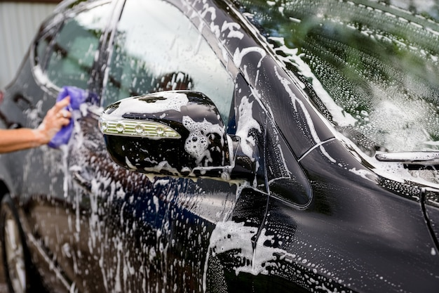 Hands hold sponge for washing car.car detailing or valeting concept. selective focus. car detailing. cleaning with sponge and cloth. worker cleaning. auto wash concept solution to clean