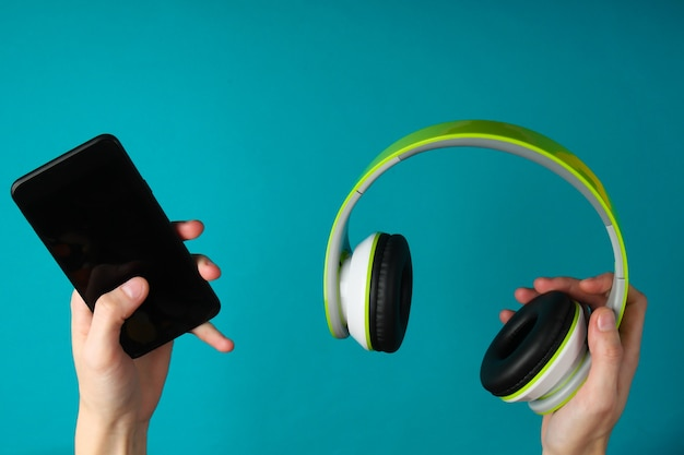 Hands hold stereo headphones and smartphone on blue surface