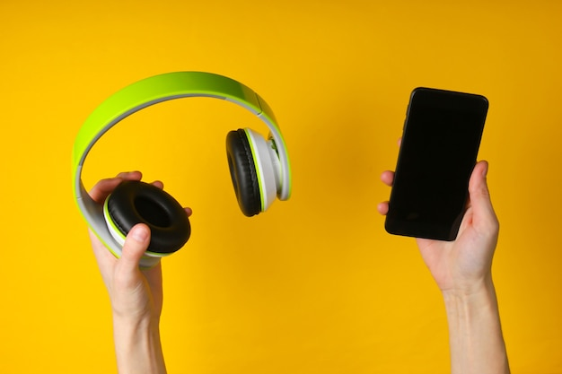 Hands hold stereo headphones and smartphone on a yellow surface
