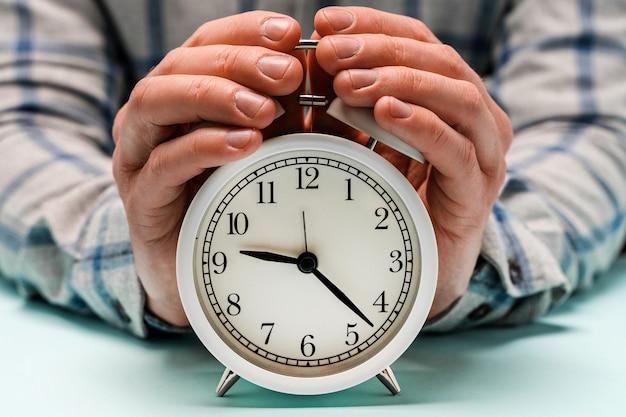 손은 알람 시계를 잡습니다. 유용하게 시간을 보내는 개념, 비즈니스 관리