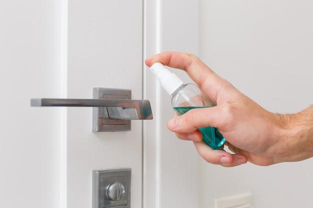 손은 방부제로 분무기를 잡고 다른 손은 소독제 용액을 적신 천으로 문 손잡이를 닦습니다.