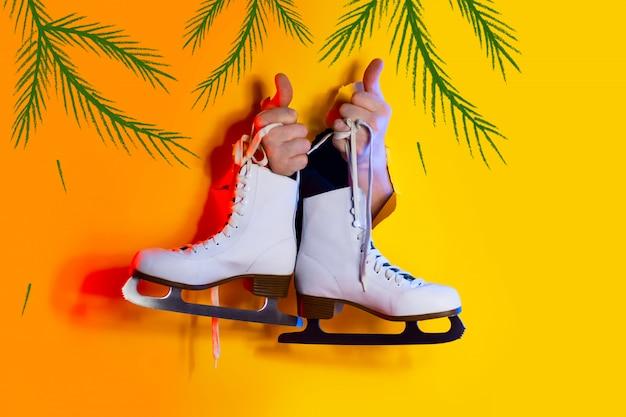 Руки держат зимние коньки за шнурки. они высовываются из дыры на желтом бумажном фоне и освещаются неоновым светом