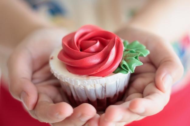 Руки держат валентинки кекс с красной розой
