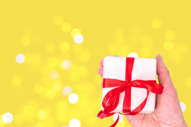 Hands hold white gift box with red ribbon