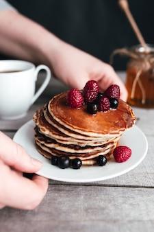 손은 팬케이크, 딸기, 꿀, 나무 테이블, 항아리 및 숟가락에 커피 컵과 흰색 접시를 잡으십시오. 고품질 사진