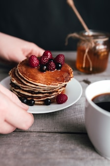 Hands hold white plate with pancakes, berries, honey, coffee cup on wooden table, jar and spoon. high quality photo