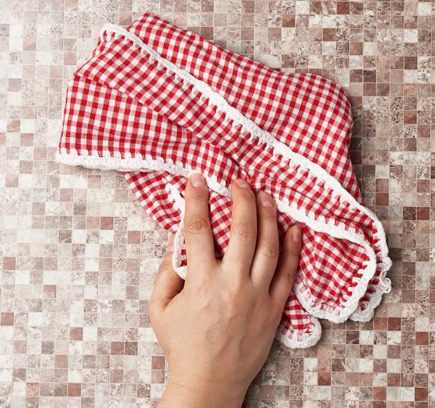 手は茶色の背景に白の赤の市松模様のキッチンタオルを保持します。