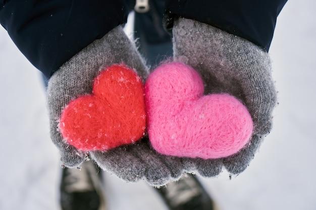 Руки держат шерстяные сердечки, покрытые снежинками на открытом воздухе зимой