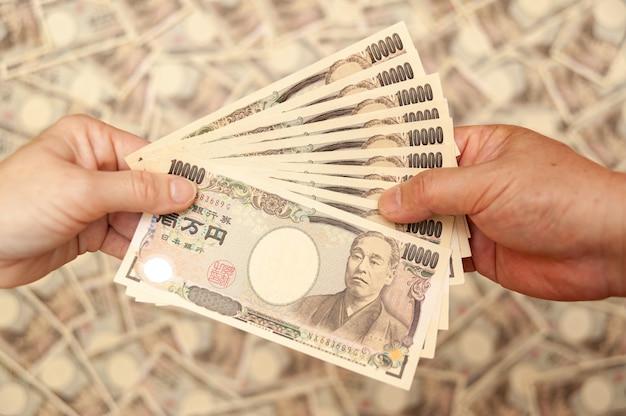 Руки, держащие банкноты 100000 иен