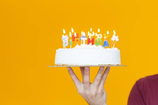 노란색 배경에 생일 케이크를 들고 촛불과 생일이라는 글자를 들고 있는 손