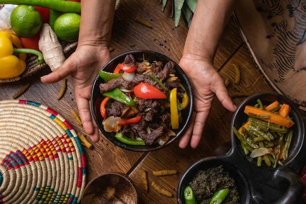Руки держат миску фахиты, мексиканской кухни