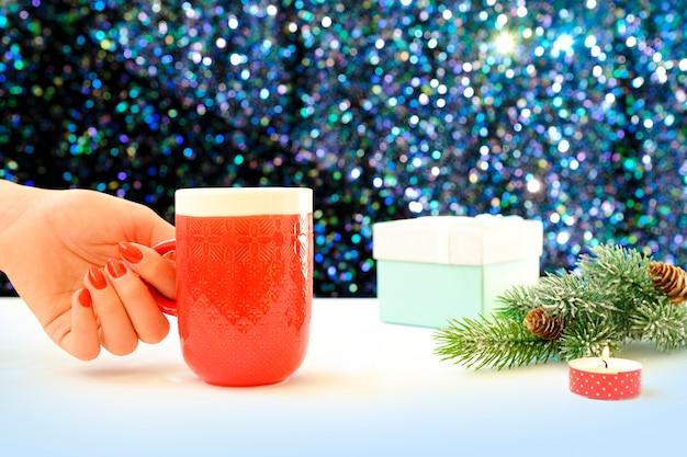크리스마스 배경에 커피 잔을 들고 손. 위에서 봅니다. 커피 컵을 들고 여성 손입니다. 크리스마스 선물 상자와 나무 테이블 위에 눈 전나무 나무.