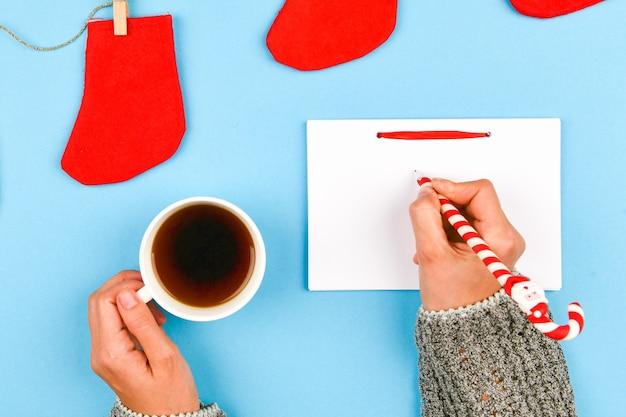 クリスマススペースにコーヒーのマグカップを保持している手。上からの眺め。コーヒーカップを保持している女性の手。クリスマスギフトボックスと木製のテーブルの上の雪のモミの木。コピースペースの平面図です。