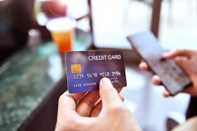 Руки держат кредитную карту и используют смартфон для онлайн-покупок