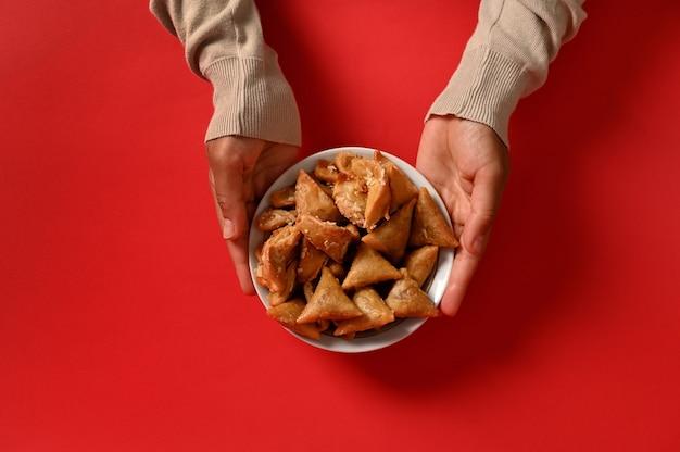 赤い背景で隔離の新鮮な伝統的なモロッコの手作りのお菓子でいっぱいの美味しくて甘いプレートを持っている手。テキスト用のスペース。お祝いのテーブルにアラビアの伝統的なオリエンタルスイーツ