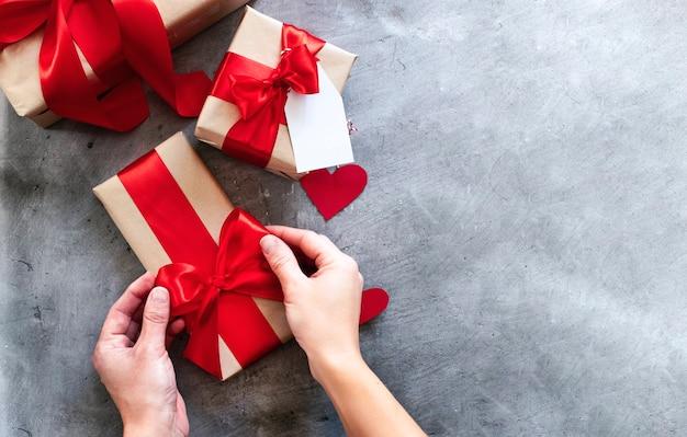 Руки держат подарочную коробку, бирку с красной лентой