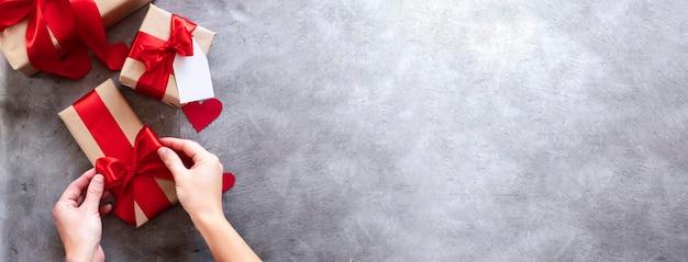 Руки держат подарочную коробку с красной лентой на сером фоне