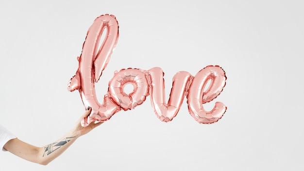 光沢のあるピンクの愛の風船を持っている手