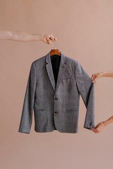 Руки держат серый пиджак в вешалке