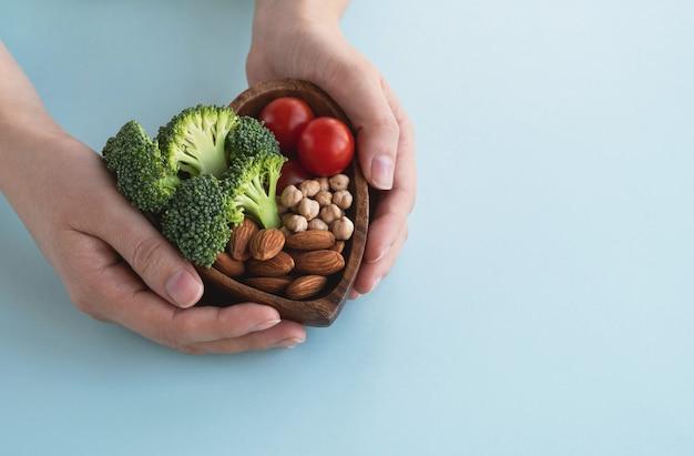 Руки, держа дерево в форме сердца здоровой пищи на синем фоне