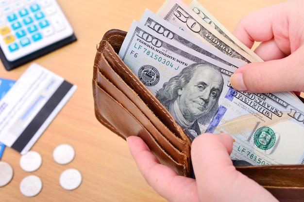 미국 달러 캐쉬인사이드가 있는 가죽 지갑을 들고 있는 손