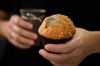 Hands holding a muffin look delicious.