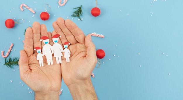 Руки держат вырезанную из бумаги семью с масками на рождество. новая нормальность из-за социальной дистанции коронавируса на рождество. скопируйте пространство.