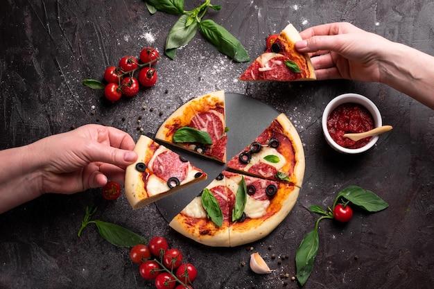 焼きたてのピザのパイを持っている手