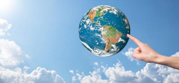 손을 잡고 행성, 아름다운 흰 구름과 햇빛과 자연 푸른 하늘의 배경에 지구. 지구 개념을 유지합니다. nasa가 제공 한이 이미지의 요소.