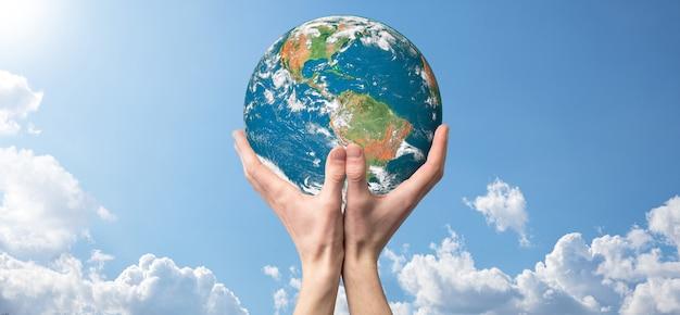 손을 잡고 행성, 아름 다운 흰 구름과 햇빛 지구 하늘. 지구 개념을 유지합니다. 제공된이 이미지의 요소