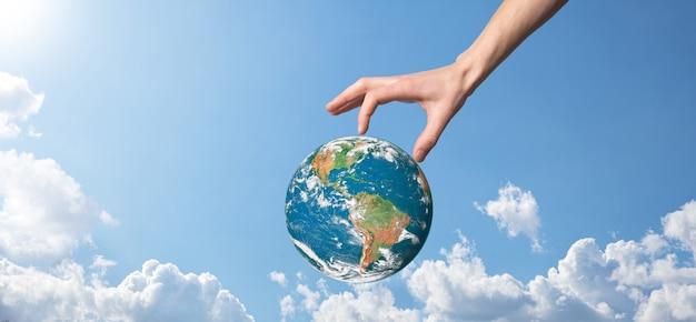 Руки держат планету, земное небо с красивыми белыми облаками и солнечным светом. поддерживают земную концепцию. элементы этого изображения предоставлены