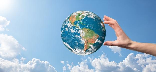 Руки держат планету, небо с красивыми белыми облаками и солнечный свет. выдержать концепцию земли. элементы этого изображения предоставлены