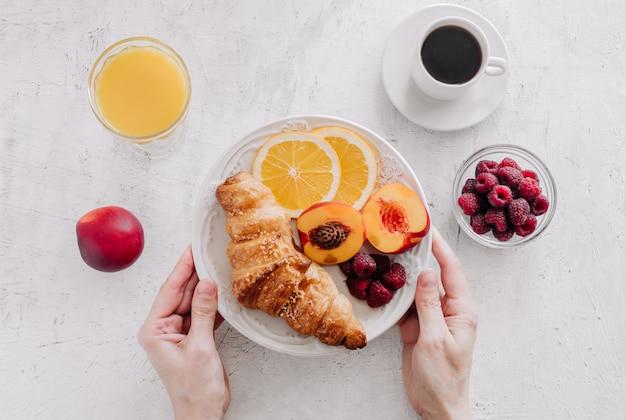 크로와 과일 접시를 들고 손