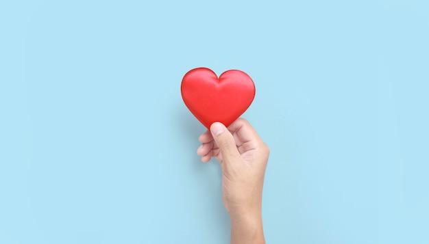 Руки держат красное сердце. концепции пожертвования здоровья сердца