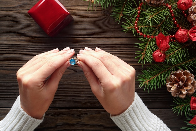 Руки держат кольцо с голубым камнем