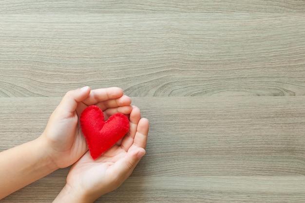 Руки держат мягкую форму сердца. день святого валентина