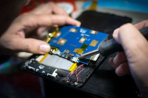 Руки держат крупный план паяльника. ремонт мобильных телефонов и планшетов