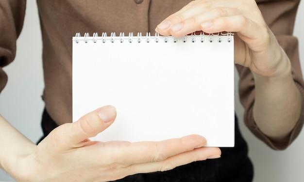 Руки держат тетрадь квадратной спирали с пустыми белыми страницами