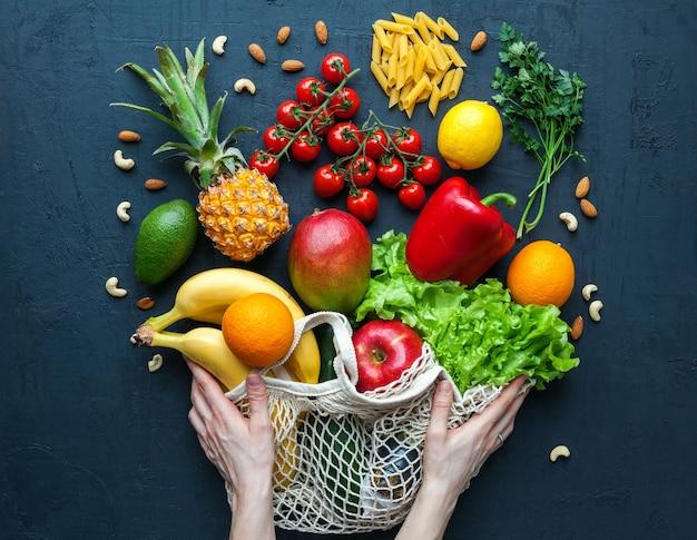 건강 한 채식 음식으로 문자열 가방을 들고 손. 다양한 야채와 과일