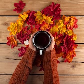 秋の紅葉とお茶を持っている手