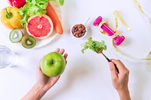 白いテーブルの上に健康食品と野菜とリンゴを保持している手。