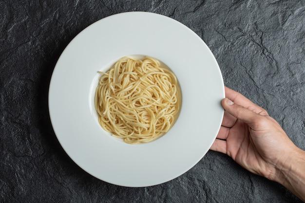 Руки держат белую тарелку, полную вкусной лапши.