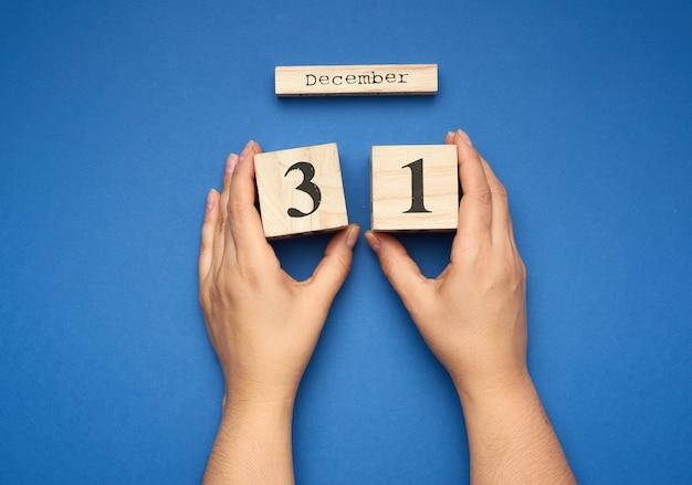 Руки держат деревянный календарь