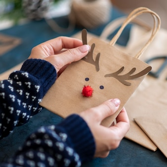 Hands holding adorable reindeer decorated christmas gift bag